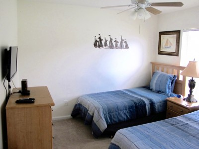 The blue room with two twin beds, tv, bureau -night stand and closet